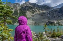 Γυναίκα στο πορφυρό σακάκι βροχής στη λίμνη βουνών στοκ φωτογραφία με δικαίωμα ελεύθερης χρήσης