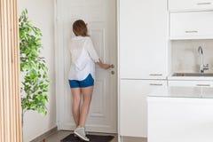 Γυναίκα στο πουκάμισο και σορτς που κοιτάζουν στην πόρτα ματάκι πόρτας όταν χτυπά κάποιος το doorbell στοκ φωτογραφία με δικαίωμα ελεύθερης χρήσης