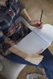 Γυναίκα στο πουκάμισο καρό που γράφει στο κενό σημειωματάριο στοκ φωτογραφίες