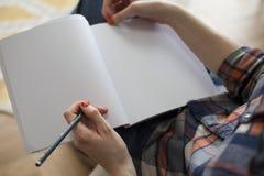 Γυναίκα στο πουκάμισο καρό που γράφει στο κενό σημειωματάριο στοκ φωτογραφία με δικαίωμα ελεύθερης χρήσης