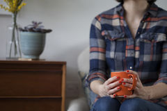 Γυναίκα στο πουκάμισο καρό που κρατά μια πορτοκαλιά κούπα στοκ εικόνα