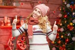 Γυναίκα στο πουλόβερ με τους αντίχειρες επάνω κοντά στο διακοσμημένο χριστουγεννιάτικο δέντρο Στοκ Φωτογραφία