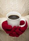 Γυναίκα στο πουλόβερ με το κόκκινο φλιτζάνι του καφέ εκμετάλλευσης γαντιών Στοκ Εικόνες