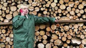 Γυναίκα στο πράσινο slicker που στέκεται κοντά στην ξυλεία, ομιλούν τηλέφωνο απόθεμα βίντεο