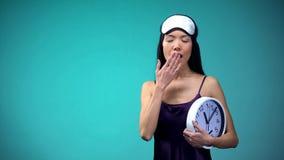Γυναίκα στο ρολόι και το χασμουρητό εκμετάλλευσης blindfold, αργά για την εργασία, αναταραχή ύπνου στοκ φωτογραφία με δικαίωμα ελεύθερης χρήσης