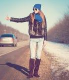 Γυναίκα στο δρόμο που κάνει ωτοστόπ, σακάκι γουνών Στοκ Φωτογραφίες
