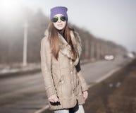 Γυναίκα στο δρόμο που κάνει ωτοστόπ, sheepskin γουνών παλτό Στοκ Εικόνα