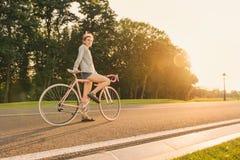 Γυναίκα στο ρόδινο ζωηρόχρωμο ποδήλατο με την έναρξη dreadlocks Στοκ εικόνα με δικαίωμα ελεύθερης χρήσης