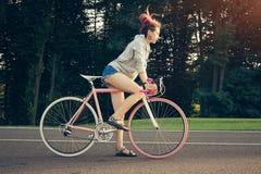 Γυναίκα στο ρόδινο ζωηρόχρωμο ποδήλατο με την έναρξη dreadlocks Στοκ εικόνες με δικαίωμα ελεύθερης χρήσης