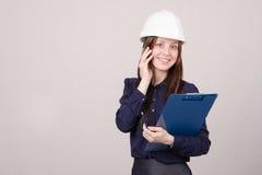 Γυναίκα στο σκληρό καπέλο που μιλά σε έναν πελάτη στο τηλέφωνο Στοκ Φωτογραφία