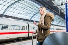 Γυναίκα στο σταθμό τρένου που χρησιμοποιεί το χρονοδιάγραμμα app στο τηλέφωνο Στοκ Εικόνα