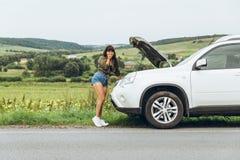 Γυναίκα στο σφιχτό νέο σπασμένο αυτοκίνητο πουκάμισων με την ανοιγμένη κουκούλα στοκ φωτογραφία