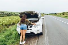 Γυναίκα στο σφιχτό νέο σπασμένο αυτοκίνητο πουκάμισων με την ανοιγμένη κουκούλα στοκ εικόνα με δικαίωμα ελεύθερης χρήσης