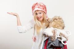 Γυναίκα στο σωρό ενδυμάτων εκμετάλλευσης χειμερινών καπέλων Στοκ φωτογραφία με δικαίωμα ελεύθερης χρήσης