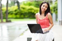 Γυναίκα στο τηλέφωνο και εργασία στο lap-top της στοκ εικόνες