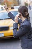 Γυναίκα στο τηλέφωνο κυττάρων που χαιρετά ένα κίτρινο αμάξι ταξί Στοκ φωτογραφία με δικαίωμα ελεύθερης χρήσης