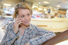 Γυναίκα στο τηλέφωνο στην περιοχή κατασκευής βαρκών Στοκ Εικόνες