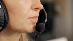 Γυναίκα στο τηλεφωνικό κέντρο που χρησιμοποιεί την κάσκα στην ομιλία με τους πελάτες φιλμ μικρού μήκους