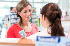 Γυναίκα στο φαρμακείο που δέχεται συμβουλές από την κυρία πωλήσεων στοκ φωτογραφία