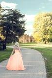 Γυναίκα στο φόρεμα βραδιού που περπατά στο σπίτι φέουδων Στοκ φωτογραφία με δικαίωμα ελεύθερης χρήσης