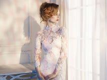 Γυναίκα στο φόρεμα δαντελλών στο παράθυρο Στοκ Φωτογραφίες