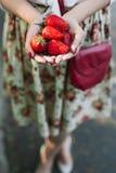 Γυναίκα στο φόρεμα λουλουδιών που κρατά μια δέσμη των φραουλών Στοκ Φωτογραφίες