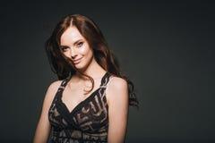 Γυναίκα στο φόρεμα, brunette με μακρυμάλλη πέρα από το σκοτεινό υπόβαθρο FEM στοκ φωτογραφία