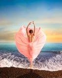 Γυναίκα στο όμορφο ρόδινο φόρεμα που χορεύει seacoast στοκ εικόνες
