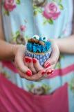 Γυναίκα στο Floral φόρεμα με τα χρωματισμένα καρφιά που κρατά το μπλε cupcake Στοκ φωτογραφίες με δικαίωμα ελεύθερης χρήσης