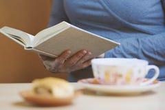 Γυναίκα συνεδρίασης που διαβάζει ένα βιβλίο σε ένα φλυτζάνι του τσαγιού και του γλυκού επιδορπίου στοκ φωτογραφίες με δικαίωμα ελεύθερης χρήσης