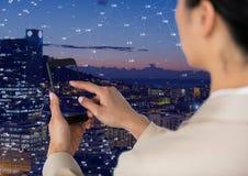 Γυναίκα σχετικά με το τηλέφωνο ενάντια στην πόλη νύχτας με τους συνδετήρες Στοκ Φωτογραφία