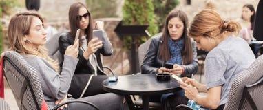 Γυναίκα τέσσερα στον καφέ που χρησιμοποιεί app το smartphone που παίζει το κοινωνικό δίκτυο Στοκ Φωτογραφία