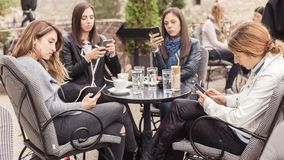 Γυναίκα τέσσερα στον καφέ που χρησιμοποιεί app το smartphone που παίζει το κοινωνικό δίκτυο Στοκ φωτογραφία με δικαίωμα ελεύθερης χρήσης