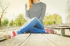 Γυναίκα τζιν παντελόνι, ριγωτή μπλούζα και κόκκινα πάνινα παπούτσια καμβά που κάθονται το ο ένας πάγκος Στοκ εικόνα με δικαίωμα ελεύθερης χρήσης