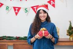 Γυναίκα της Ασίας στο δώρο κομμάτων Χριστουγέννων που δίνει το χρυσό κιβώτιο στο φίλο με το SMI Στοκ Εικόνα