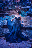 Γυναίκα της Ασίας στο μαύρο μακρύ φόρεμα που στέκεται στο δάσος Στοκ Εικόνα