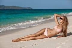 Γυναίκα της Tan χαλκού που κάνει ηλιοθεραπεία στην τροπική παραλία Στοκ Εικόνες
