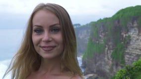 Γυναίκα τουριστών πορτρέτου στο τοπίο κυμάτων βουνών και νερού απότομων βράχων στην ωκεάνια ακτή Χαμογελώντας γυναίκα στην άκρη α φιλμ μικρού μήκους