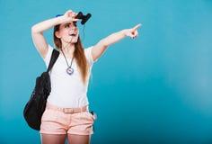 Γυναίκα τουριστών που κοιτάζει μέσω των διοπτρών στο μπλε Στοκ Εικόνες