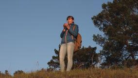 Γυναίκα τουριστών που πίνει το καυτό τσάι και που προσέχει το ηλιοβασίλεμα ταξιδιώτης κοριτσιών, στάσεις πάνω από έναν καφέ καταν απόθεμα βίντεο