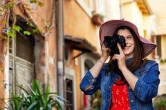 Γυναίκα τουριστών στο καπέλο που παίρνει τους πυροβολισμούς με τη κάμερα στοκ εικόνες