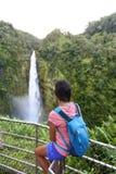 Γυναίκα τουριστών ταξιδιού της Χαβάης που εξετάζει τον καταρράκτη Στοκ Φωτογραφίες