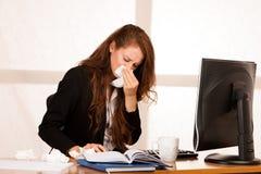 Γυναίκα του IL που υποφέρει στην εργασία πίσω από το γραφείο στο γραφείο της Στοκ εικόνες με δικαίωμα ελεύθερης χρήσης