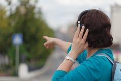 Γυναίκα υπαίθρια στη μουσική ακούσματος πόλεων με τα ακουστικά Στοκ Εικόνες