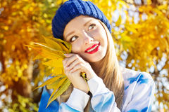 Γυναίκα φθινοπώρου ευχαριστημένη από τα ζωηρόχρωμα φύλλα πτώσης Στοκ Εικόνα