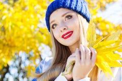 Γυναίκα φθινοπώρου ευχαριστημένη από τα ζωηρόχρωμα φύλλα πτώσης Στοκ εικόνες με δικαίωμα ελεύθερης χρήσης