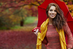 Γυναίκα φθινοπώρου στο πάρκο φθινοπώρου με την κόκκινα ομπρέλα, το μαντίλι και το δέρμα Στοκ Εικόνα