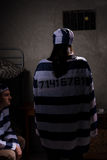 Γυναίκα φυλακισμένος που φορά την ομοιόμορφη στάση φυλακών με το πίσω ΝΕ της Στοκ εικόνα με δικαίωμα ελεύθερης χρήσης