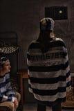 Γυναίκα φυλακισμένος που φορά την ομοιόμορφη στάση φυλακών με το πίσω ΝΕ της Στοκ φωτογραφία με δικαίωμα ελεύθερης χρήσης