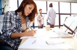 Γυναίκα φωτογραφιών που εργάζεται με το νέο πρόγραμμα ξεκινήματος στη σύγχρονη σοφίτα Γενικό σημειωματάριο σχεδίου στον ξύλινο πί στοκ φωτογραφία με δικαίωμα ελεύθερης χρήσης